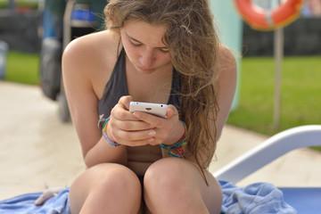jeune fille avec son portable au bord de la piscine