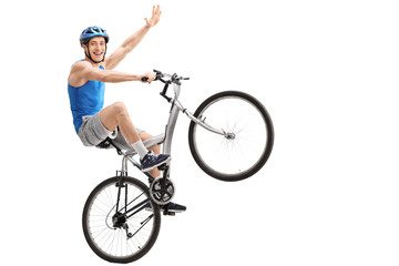 Confident young biker performing a wheelie