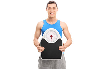 Young athlete holding a weight scale