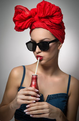 Woman with red turban and sunglasses drinking from a bottle with a straw. Attractive girl portrait holding a bottle, studio shot on gray background. Happy young female, advertisement concept
