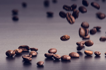 Coffee beans on a black background. Levitation of coffee beans. Raw coffee beans. Grained product. Hot drink. Close up. Harvesting. Natural background. Energy