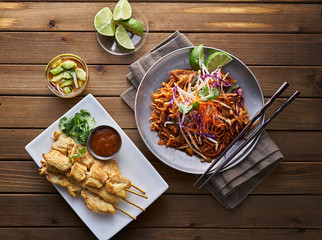 beef pad thai and chicken satay dinner viewed from above