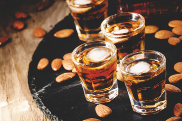 Brandy and almonds, small glasses on a dark background, selectiv