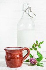 Fresh milk in ceramic mug, old fashioned bottle and wildflowers