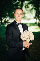 Handsome young groom posing outside in nature