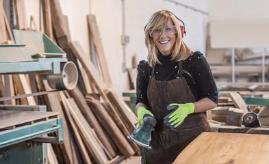 Female carpenter Using Electric Sander / Female carpenter Using Electric Sander for wood