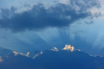 Sky and clouds. Storm cloud with a luminous edge and rays of the sun.