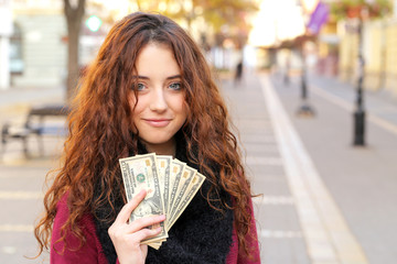 young shopper woman showing money on street