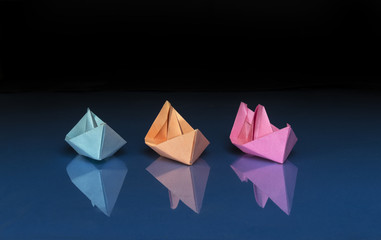 three colored paper boats