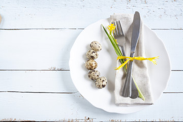 Easter table setting with spring flowers, eggs and cutlery. Holidays background with quail eggs, white plate, cutlery, napkin, ribbons and daffodil (yellow narcissus) on light table.