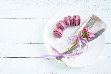 Table setting with spring flowers, crimson french macaroons and cutlery. Holidays background.