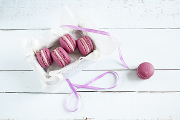 Sweet crimson french macaroons with box on  light dyed wooden background