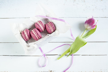 Sweet crimson french macaroons with box and tulip on  light dyed wooden background
