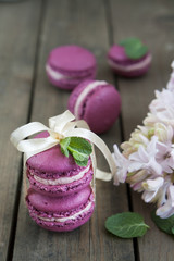 Sweet crimson french macaroons tied with ribbon with hyacinth and mint on dark wooden background