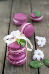 Sweet crimson french macaroons tied with ribbon wiht hyacinth flowers and mint on dark wooden background
