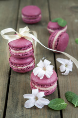Sweet crimson french macaroons  wiht hyacinth flowers and mint on dark wooden background
