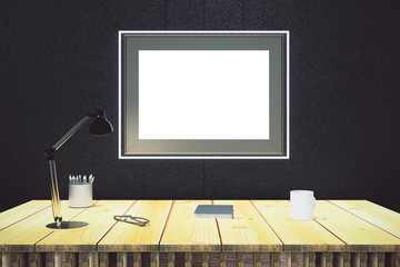 Blank picture frame on black wall with wooden table with lamp an