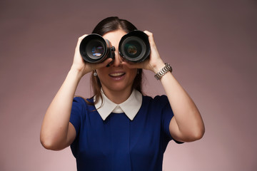 Girl in a blue suit. Makes binocular by two photo lenses.