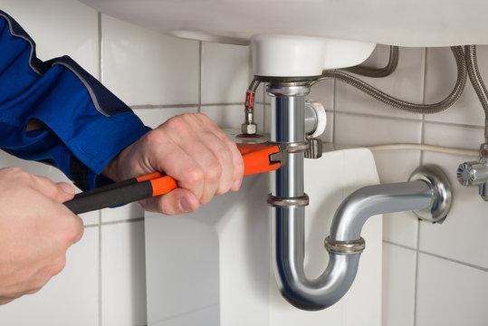 Male Plumber Repairing Sink In Bathroom