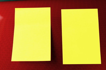 Two yellow reminder notes on a portable computer red patterned