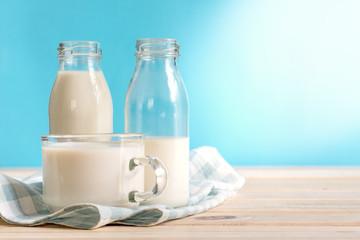 Milk bottle and milk glass put on wooden.