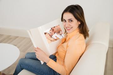 Woman Sitting On Sofa With Photo Album
