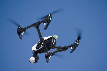 A high tech photography drone closeup as it is flying by overhead with its tracking light glowing