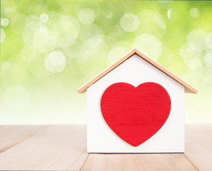 Home and red heart on wood with bokeh background