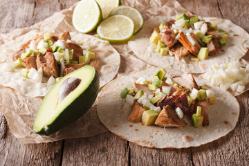 Mexican tacos with carnitas, onions and avocado close-up. horizontal