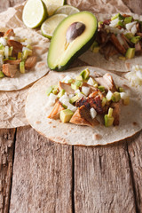 Mexican food: tortilla with carnitas, onions and avocado close-up. vertical