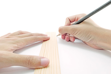 drawing a line down on paper with a ruler and pencil with both h