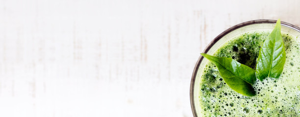 green herbal detox drink made of spinach on white wood