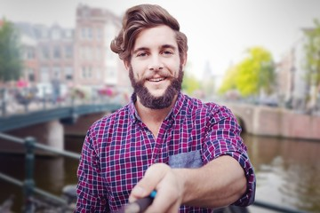 Composite image of portrait of hipster using selfie stick