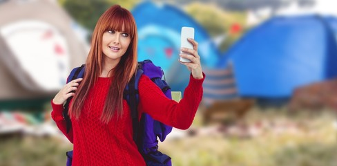 Composite image of smiling hipster woman with a travel bag taking a selfie