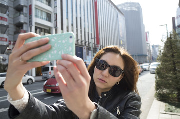 Young women who are shooting yourself in the smartphone