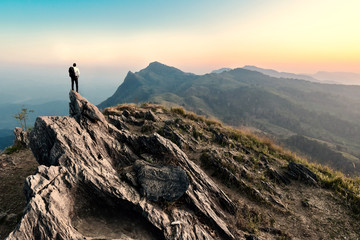 businessman hike on the peak of rocks mountain at sunset, succes
