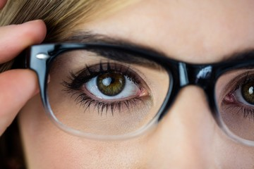 Close-up of woman touching her glasses
