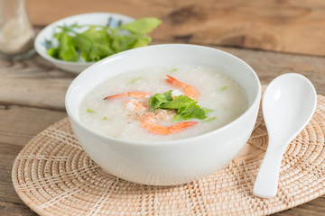 Rice porridge with shrimp in white bowl.