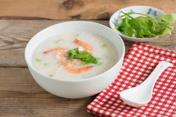 Rice porridge with shrimp in white bowl.