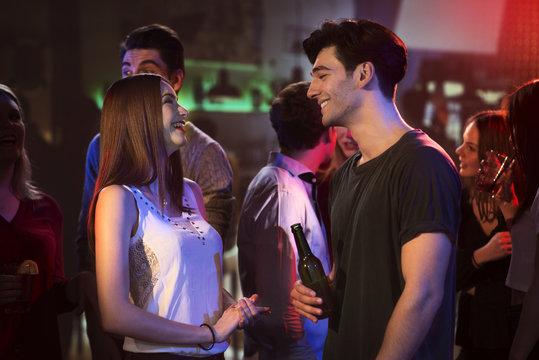 Men and woman flirting at the danceflloor in a bar