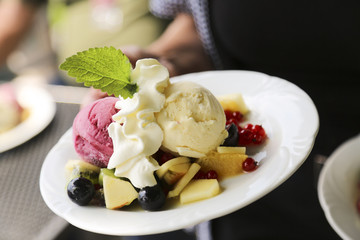 Ice cream with fruits and whipped cream