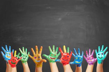 Viele bunt bemalte Kinderhände vor Tafel
