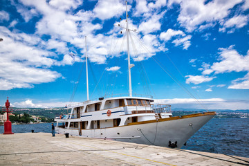 Sailing yacht in the port with blue sky and clouds