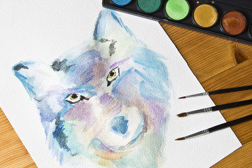 Watercolor painted picture Wolf. Brushes and painting watercolor set on wooden background. Modern art. Leisure. Artistic retouching.