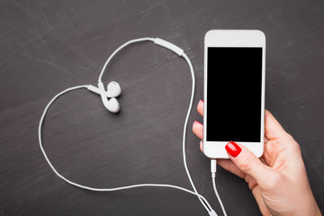 Woman holding smartphone with heart shaped headphones in background