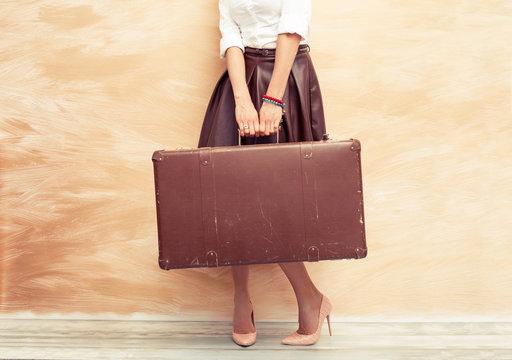 Woman holding retro suitcase