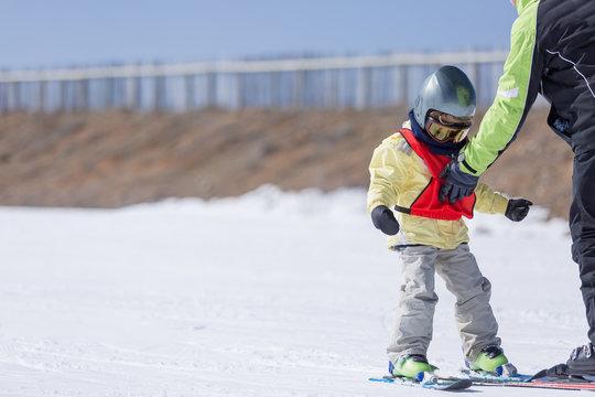 Man teaching son skiing