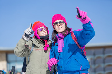 Two women skiers pointing