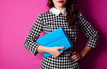 Wall Mural - fashionable young woman in stylish suit with blue handbag