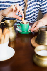 Woman dipping biscuit in coffee. Selectve focus